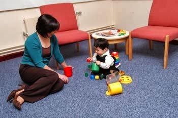 Dziecko i dorosły siedzą na dywanie, wokół zabawki. Wspólnie układają klocki